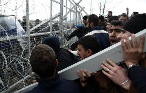 Flüchtlinge versuchen den Zaun einzureißen, damit sie die Grenze überqueren können.